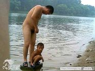 father and son having bath at river