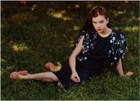 Hailee Steinfeld poses pensively on a lush lawn, and makes us all want
