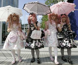 Japanese women dressed in Lolita fashion walk in front of the venue of