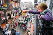 Mardi Gras reveler dangles a pair of beads off of a balcony on