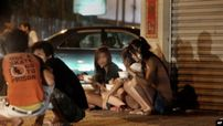 Cambodian sex workers sit on a sidewalk in a street of Phnom Penh