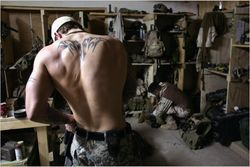 Art : Shirtless, tattooed SEAL dresses in makeshift locker room