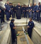 The body of the late Pope John Paul II is exhumed from the crypt of St