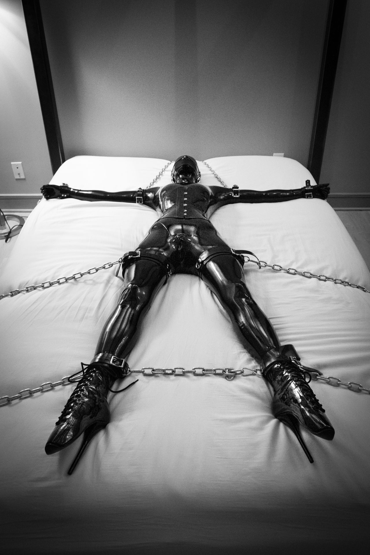 Covered in latex and chained to the bed