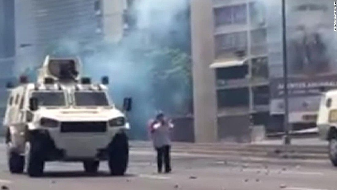 Woman stands up to armored military vehicle