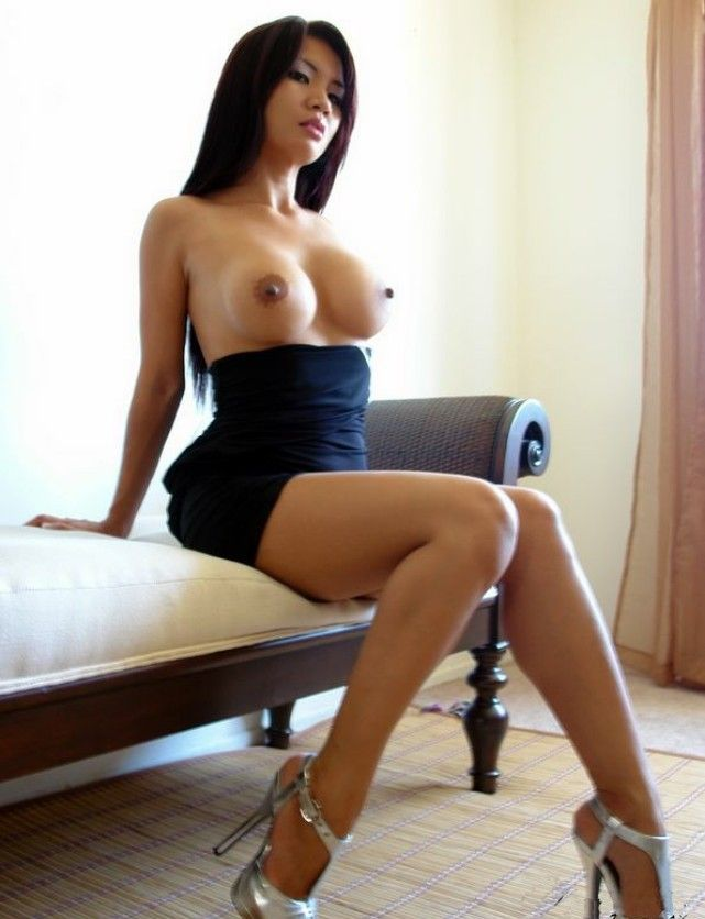 Busty asian girl posing on sofa