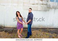 young couple poses for some engagement photos in urban outdoor