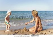 Mom and son building a sand castle on a beach  stock photo