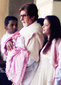 Amitabh Bachchan carries his new born grand-daughter along with his