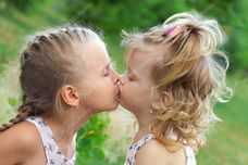 Two beautiful sisters kissing in summer park — Stock Image