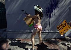 Sao Paulo, Brazil: a topless Femen activist squirts ink on the wall