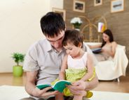 Young father reading a book to his daughter � Stock Photo � Sergey