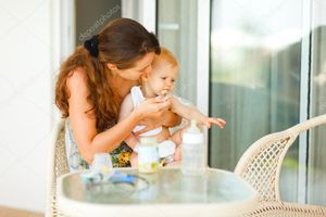 Young mama feeding look aside little baby at terrace | Stock Photo