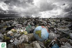 "photoshopped""  An inflatable globe lies abandoned in a rubbish dump"