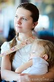 Young mother holding her sleeping daughter at airport while waiting