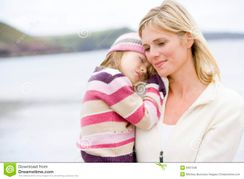 Mother Holding Sleeping Daughter At Beach Royalty Free Stock Images
