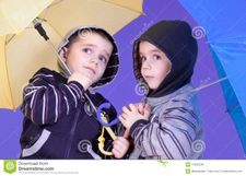 Twins Brother Have Fun Under An Umbrellas Royalty Free Stock Images