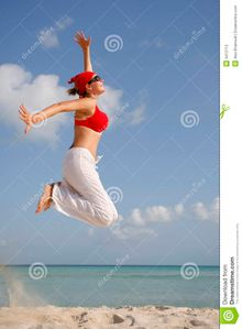 woman in red clothes jumping on a beach spanishale dreamstime com