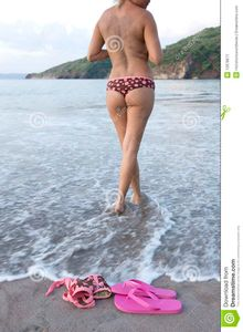 Topless woman in polka dot bikini standing in water on tropical beach