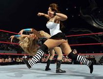 Trish evades Mickie James's clothesline with the MaTrish