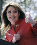 Sarah Palin flashes a thumbs up towards her husband Todd as she begins