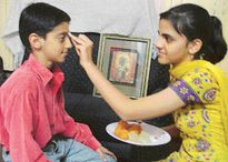 sister applies teeka on the forehead of her brother to celebrate