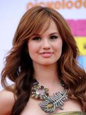 Debby shimmered in a gold strapless dress and strappy black patent