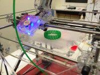 Ein «RapMan» Drucker druckt aus grünem Material ein Armband. / © Trinckle