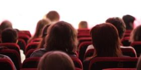 Some spectators sitting on a red soft chairs in auditorium