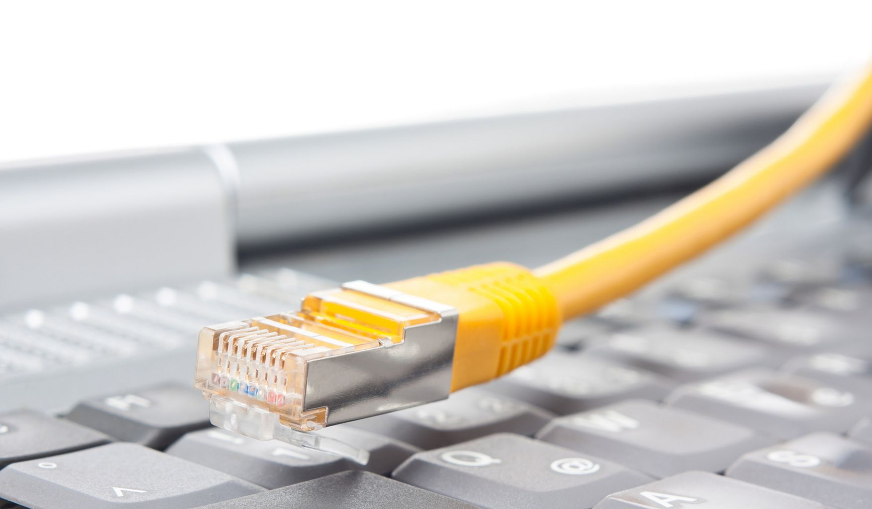 Macro of a yellow network cable in front of a keyboard