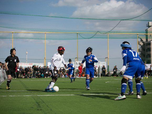 Internationaler Blindenfußball: Angriffsspieler Kofi Osei im Dribbling gegen drei Japaner beim Normalization Cup in Omiya, Japan.
