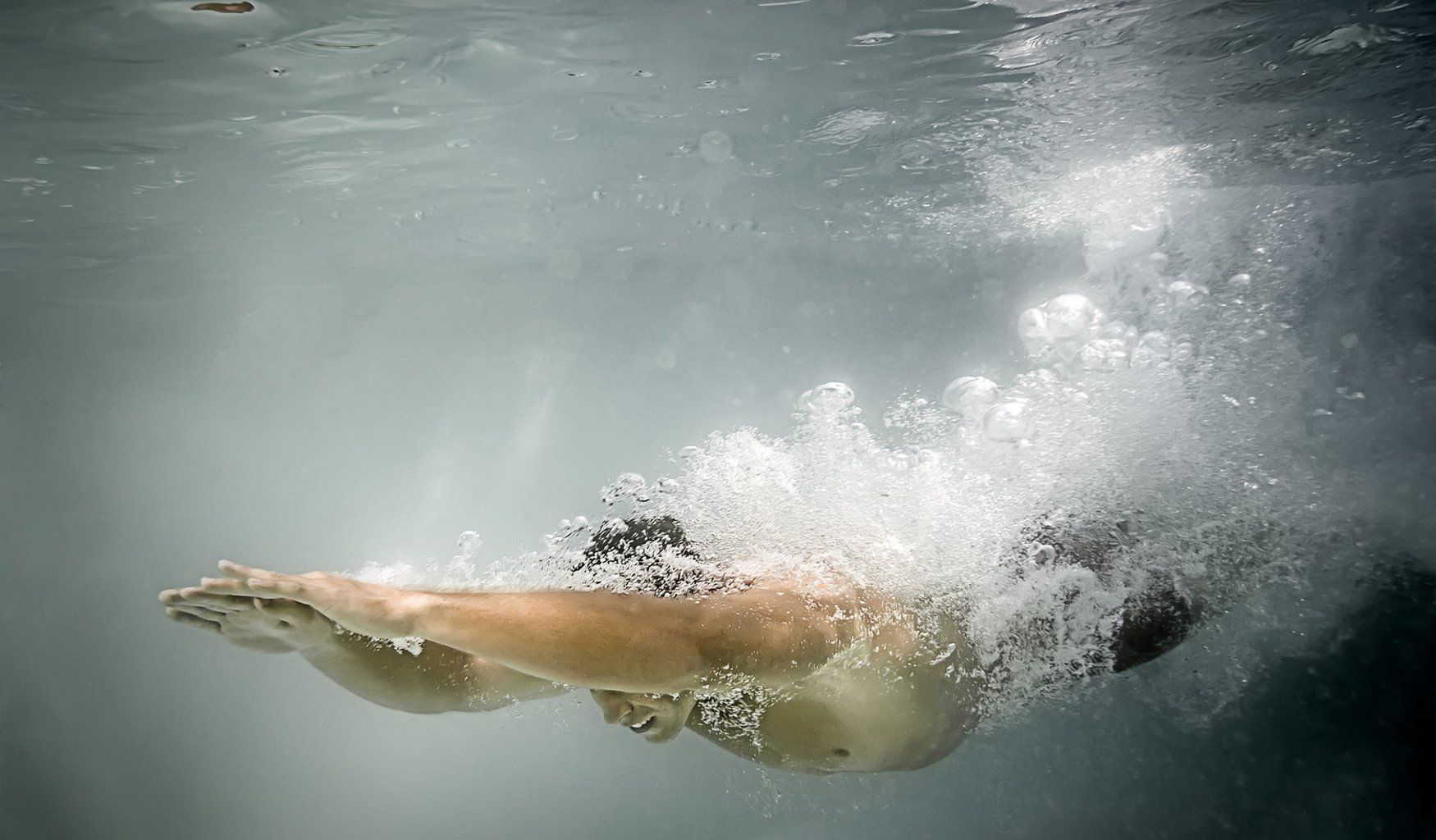 An image of a man diving in the pool with lots of air bubbles