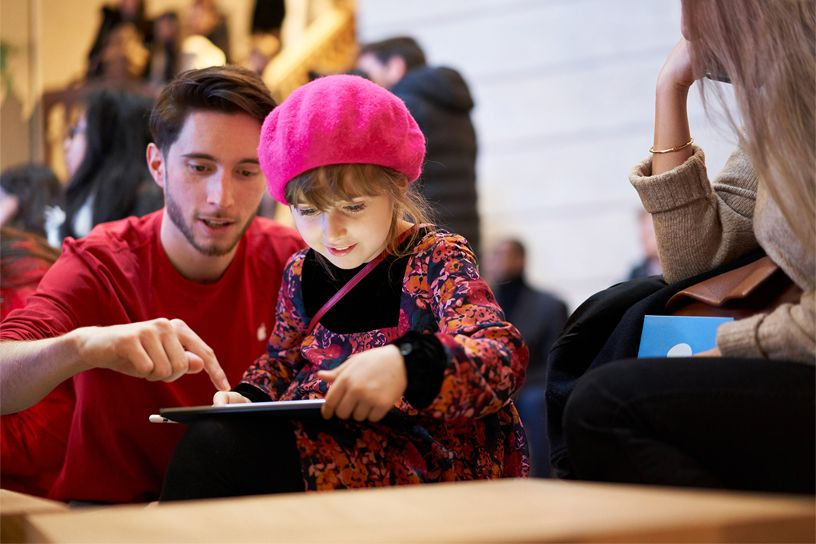 Apple team member showing a little girl how to use iPad.