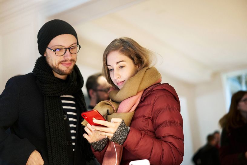 Two customers using the red iPhone XR.