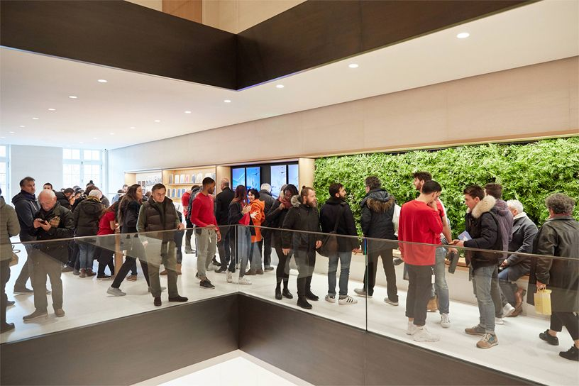 Team members and customers standing in front of a green wall at Apple Champs-Élysées.