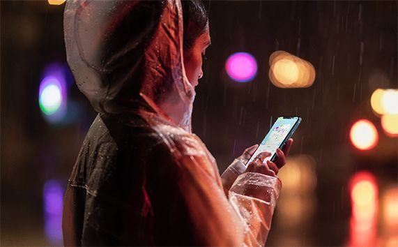 Woman holding iPhone XR in the rain.