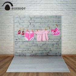 Allenjoy baby girl's pink onesie bib dress and red shoes dry on a rope against a white brick wall photography backdrops a photo