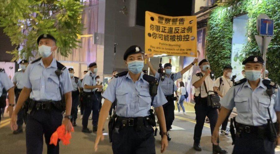 军装警员64日晚在铜锣湾渣甸坊一带举牌警告,驱散聚集悼念六四市民。(美国之音汤惠芸)