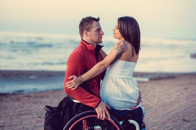 Homme en chaise roulante avec une femme assise sur ses genoux.