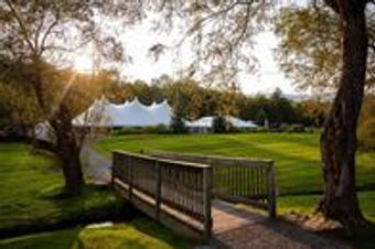 Vast open field set up with white tents for outdoor wedding