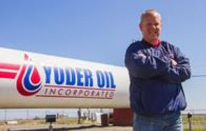 Josh Yoder in front of a large fuel tank