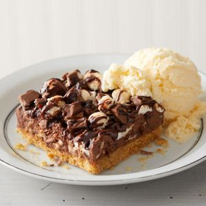 The s'mores bar is campfire favorite made more craveable. Chocolate, chocolate chunks and marshmallow sit atop a graham cracker crust and are served with a scoop of ice cream.