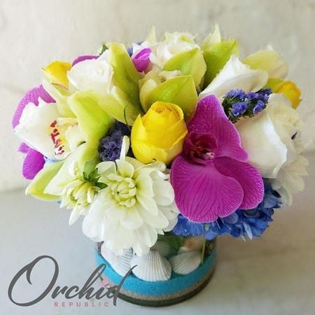 Yellow roses, white dahlias, blue hydrangeas, green cymbidium orchids, and purple phalaenopsis orchids.
