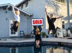 Maureen with clients sold sign