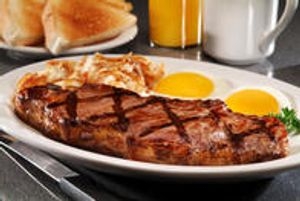 Strip steak breakfast meal with steak, 2 eggs, hash browns, toast, orange juice and coffee on table with butter knife