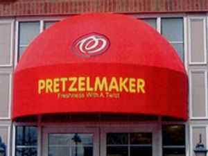 Custom Signs and Awnings - Curved Door Awning for Retail Business with custom graphics and sign printing.