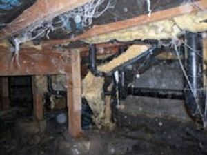 A crawl space that is in need of a clean out!