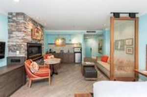 Margaritaville Island Hotel guest room fireplace, sitting area and wet bar.