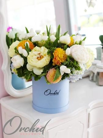 All your flower wishes coming true in one gorgeous garden style flower arrangement. Blooming with white peonies, white tulips, yellow dahlias, and baby blue hydrangeas.