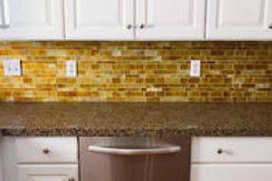Metropolis Honey mosaic tile backsplash with Terra Ombra granite countertops.